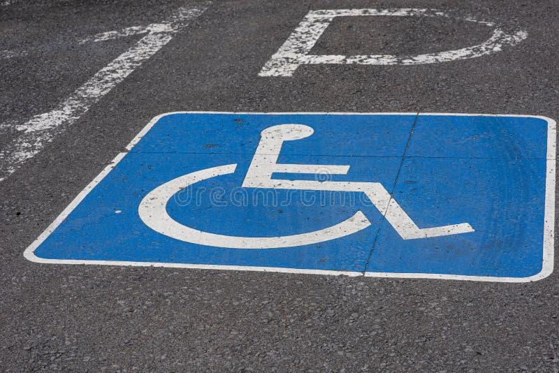 Closeup of a blue handicap sign painted on asphalt street near a park. royalty free stock photography