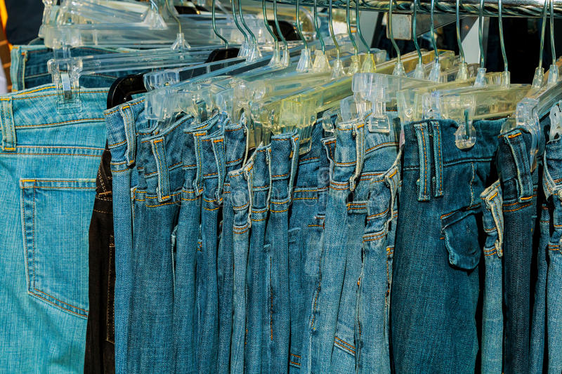 closeup of blue jeans in a shop stock images
