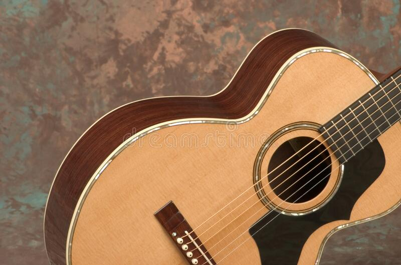 Closeup of the body of an acoustic guitar under the lights against a marble background. A closeup of the body of an acoustic guitar under the lights against a royalty free stock photography
