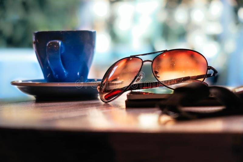 Closeup bokeh shot of aviator type of glasses with a blue cup of coffee with a blurred background stock photos