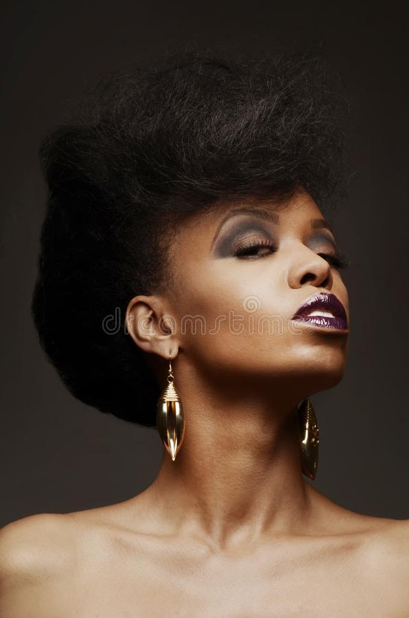 Bold African American woman with a fierce hairstyle and makeup. Closeup of a bold African American woman with a fierce hairstyle and makeup royalty free stock photos