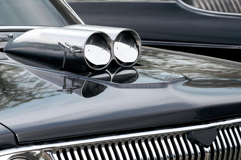 Closeup of a bonnet tuning to increase the power of a chrome turbine antique vintage black cars. royalty free stock photos