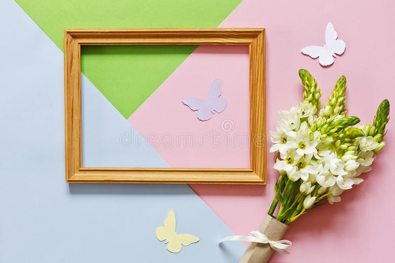 Closeup of the bouquet of white flowers, wooden frame and silhouettes of butterflies on the Pastel colors background stock photos