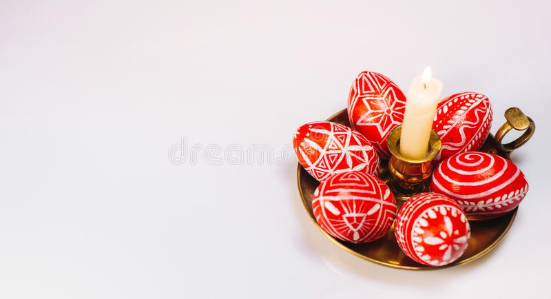 Closeup brass candlestick with Easter red eggs with folk white pattern stand on white background and eggs scattered around. Ukrain. Ian traditional eggs pisanka royalty free stock images