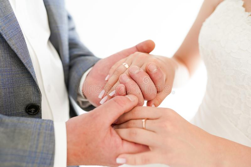 Closeup of a bride and groom holding hands isolated over a white background stock photos