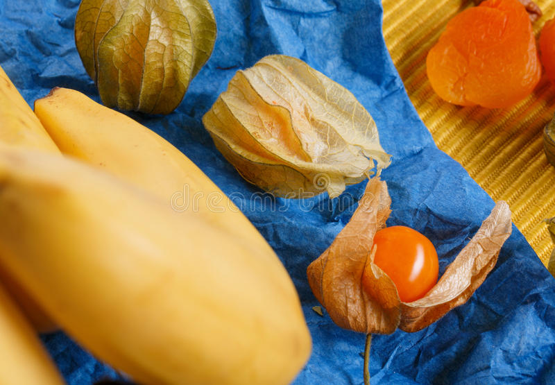 Closeup of bright unpeeled physalis, yellow bananas, orange dried apricots on napkin on a colorful background. royalty free stock photography