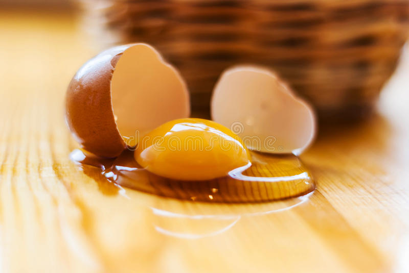 Closeup of broken egg on the kitchen table, basket defocuses. Gr. Unge background royalty free stock photography