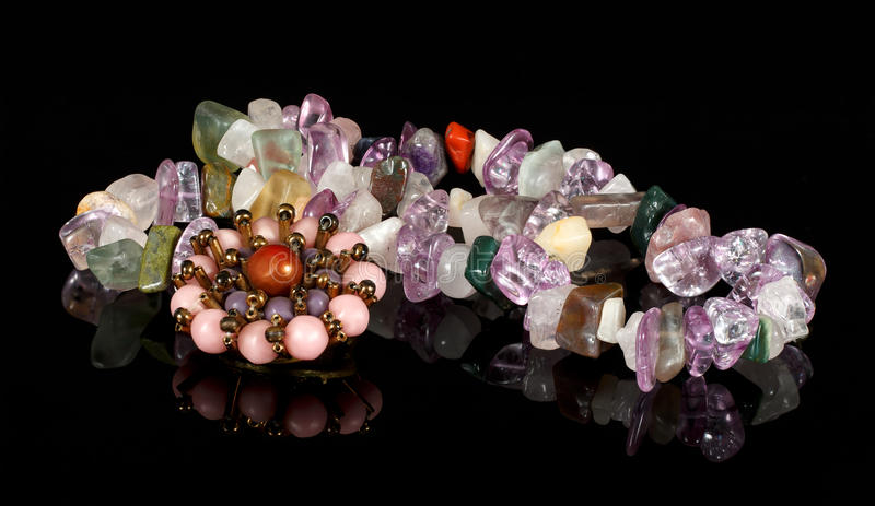 Closeup brooch and beads from crystals of amethyst, fluorite, jasper, carnelian and rose quartz on black acrylic royalty free stock images