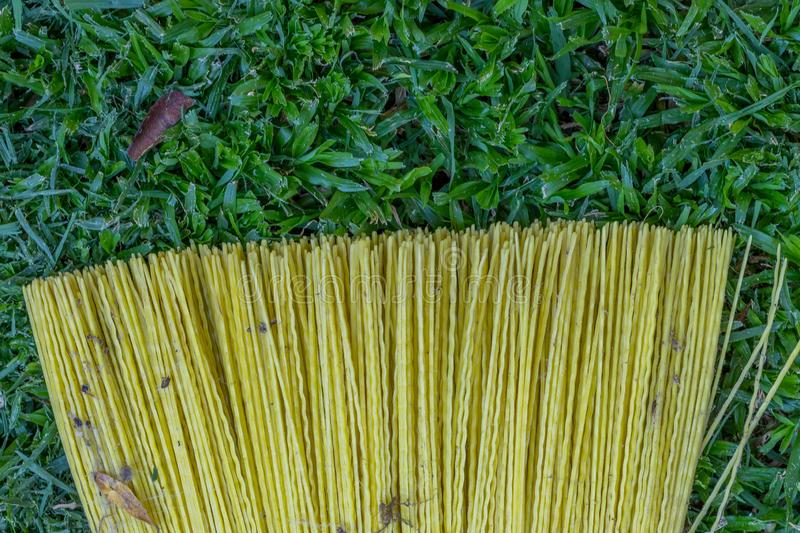 Closeup of broom bristles on a lawn. Closeup view of the yellow bristles of a garden broom isolated on a green lawn stock photo