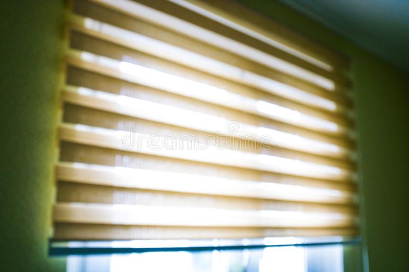 Closeup brown color Roller blinds curtains. sunlight through the windows and roller blind in the city. Soft focus image royalty free stock photo
