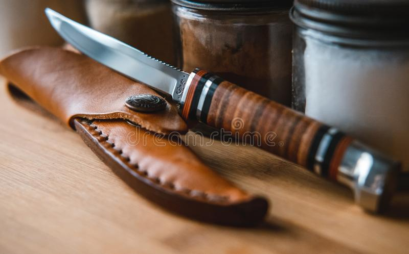 Closeup of a brown knife with a case surrounded by spice jars on a wooden table under the lights. A closeup of a brown knife with a case surrounded by spice jars stock photography