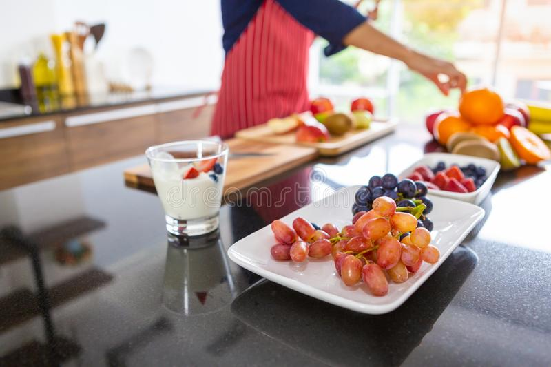 Closeup bunch of grapes on white plate and assorted fruits royalty free stock photo