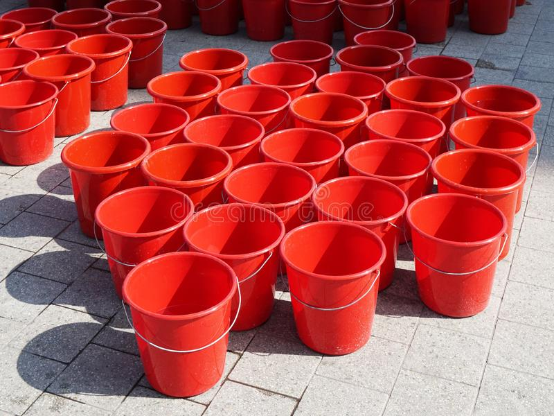 Closeup of a bunch of red buckets on cement placed close to each other stock photos