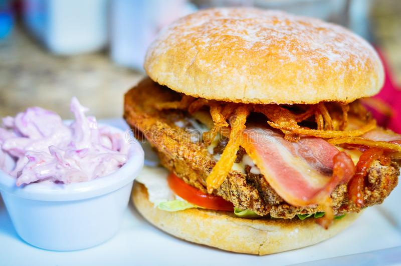 Burger with Chicken, Bacon and Fried Onions. Closeup of Burger with Chicken, Bacon, Fried Onions & Coleslaw royalty free stock photo