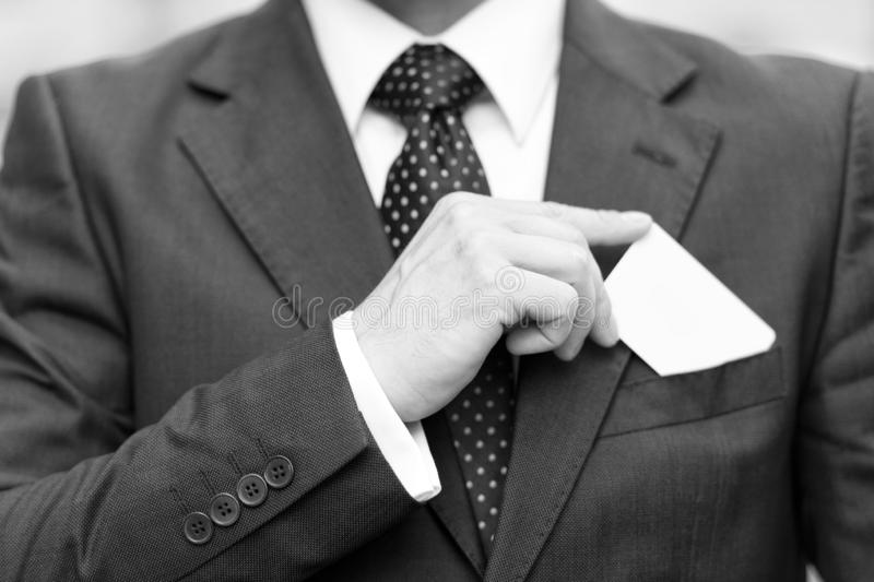 Closeup of business card in man hand holds over suit pocket. Businessman in suit drawing white business card into p. Closeup of man hand holds business card over stock photography