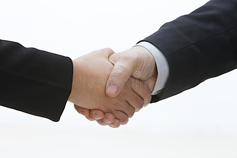Closeup of a business hand shake between two colleagues royalty free stock images