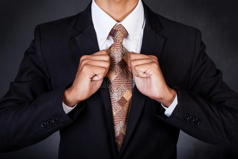 Closeup of business man fixing his neck tie royalty free stock photography