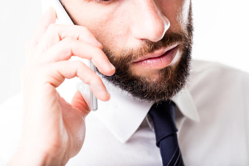 Closeup of a business man speaking on the phone. Mobile phone closeup in the hands of a serious businessman with a beard, he is listening to his customer or a stock photo