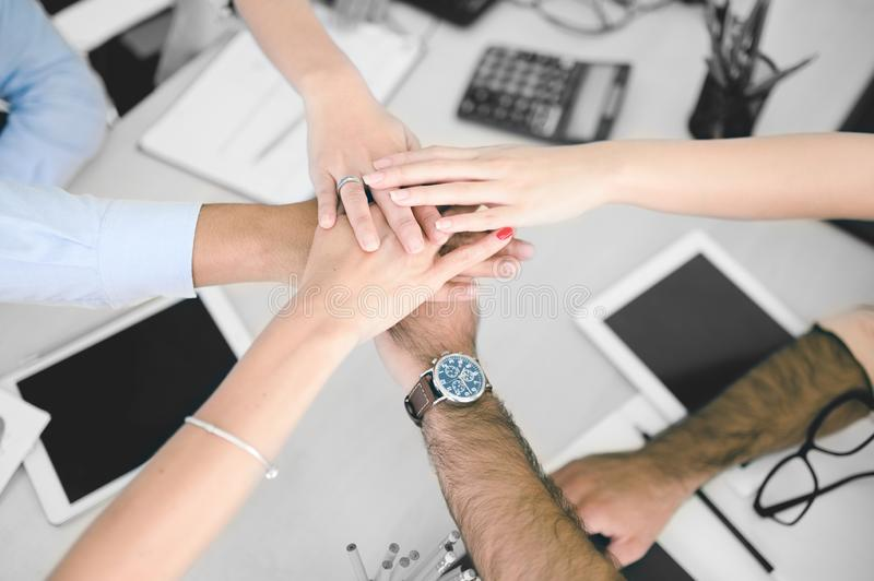 Closeup of business team putting their hands on top of each other royalty free stock image