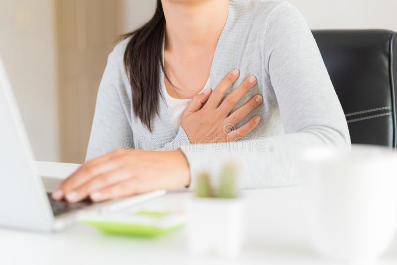 Closeup business woman having heart attack. Woman touching breast and having chest pain after long hours work on computer. Office stock image