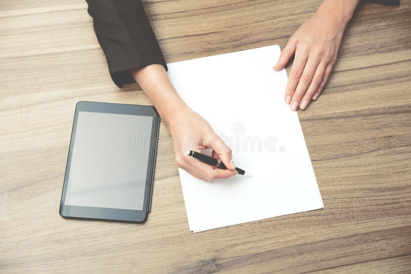 Closeup of a business woman's hands while writing down some essential information. royalty free stock photos