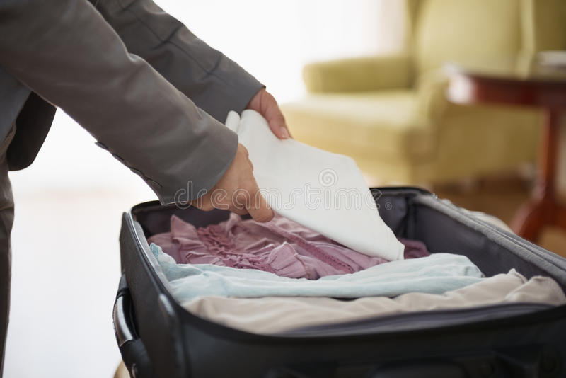 Closeup on business woman unpack luggage in hotel. Room stock image