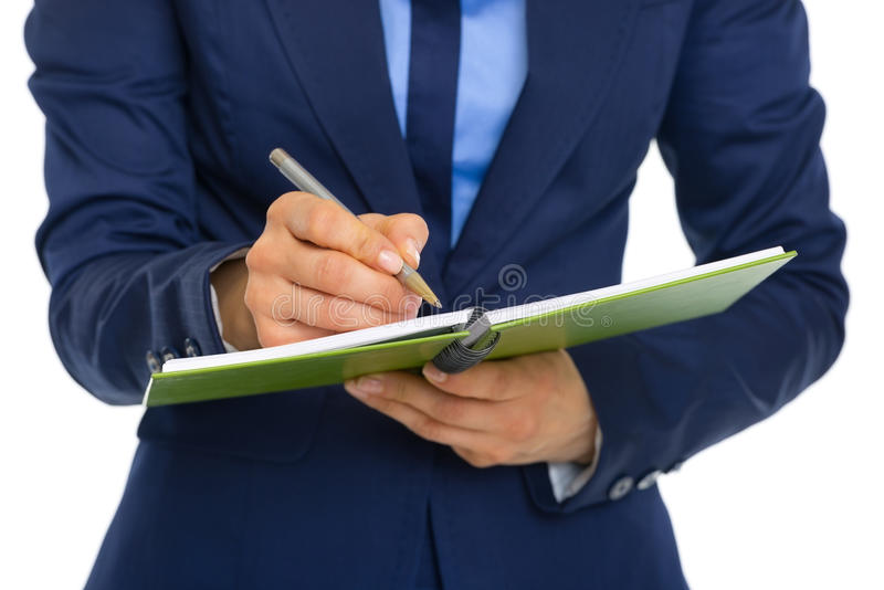 Closeup on business woman writing in notepad royalty free stock image