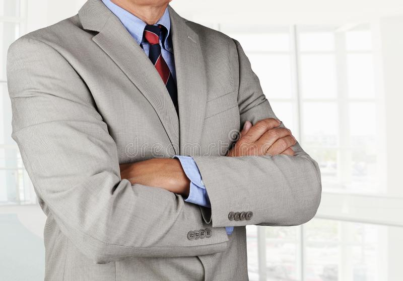 Closeup of a businessman with his arms folded in an office interior stock image