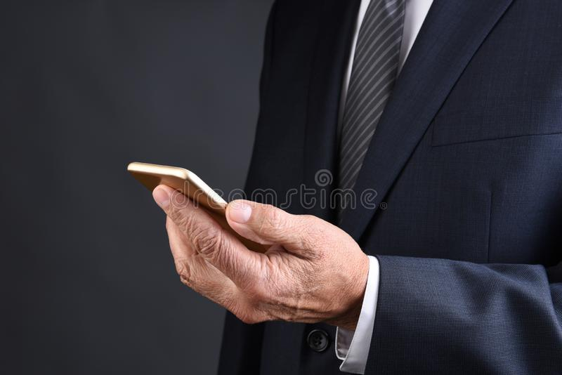 Closeup of a businessman holding his cell phone. Man is unrecognizable and phone altered royalty free stock photo