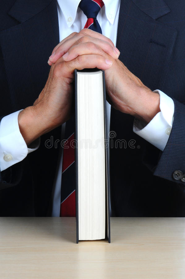 Download Closeup Of A Businessman Leaning On Book At Desk Royalty Free Stock Photography - Image: 23654647