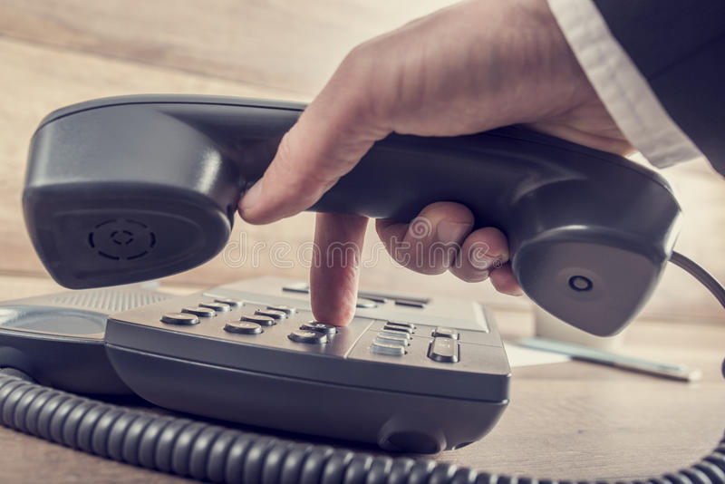 Closeup of businessman making a telephone call by dialing a phon. E number on a classical black landline device with a retro faded look royalty free stock images