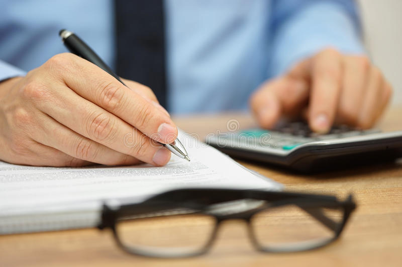 Closeup of businessman reviewing financial document and calculating costs.  stock photography