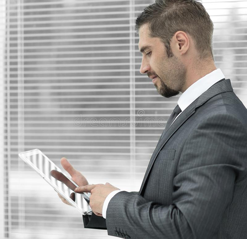 Closeup. businessman with tablet computer standing by the window. stock photos