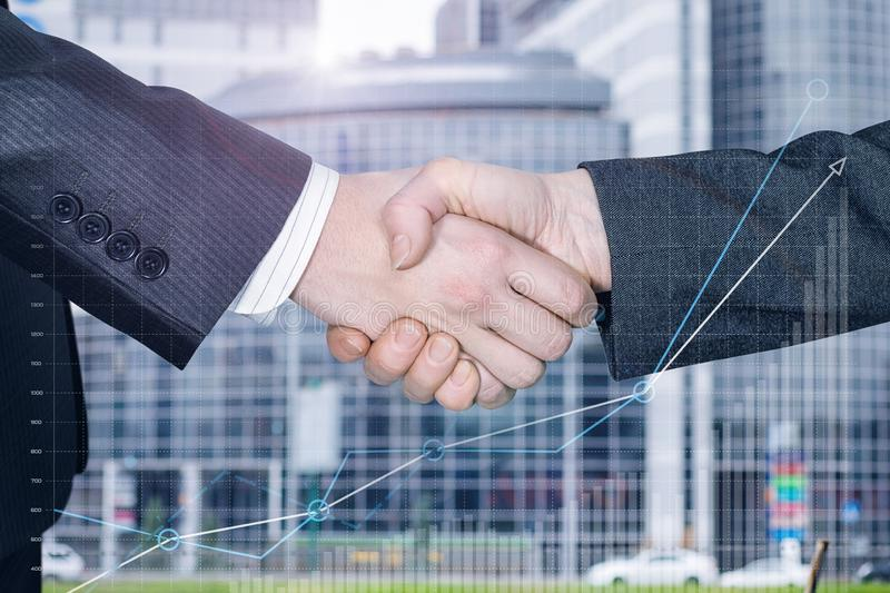 Two businessmen partners are shaking hands stock images