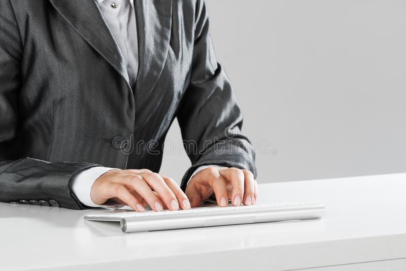 Closeup of businesswoman hand typing on keyboard with mouse on wood table stock image