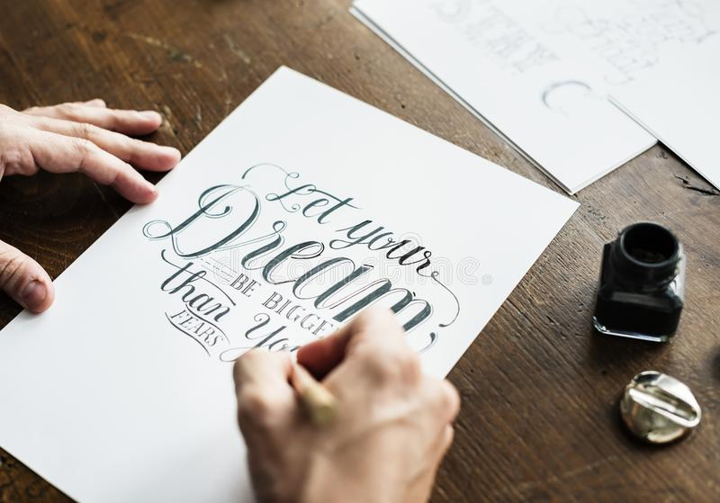 Closeup of a calligrapher working on a project stock image