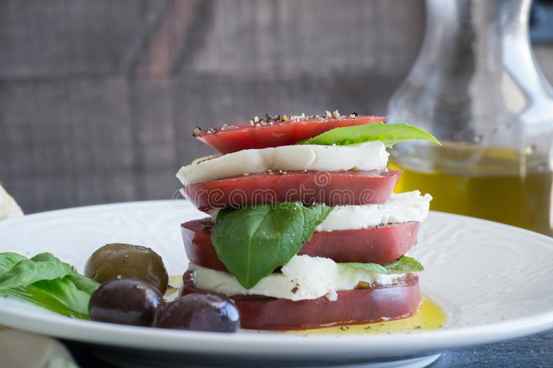 Closeup Caprese Salad with sliced red tomato, buffalo mozzarella, basil leaves and healthy whole olives dripping in extra virgin o royalty free stock photos