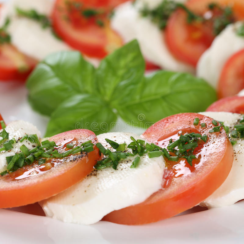 Closeup Caprese salad with tomatoes and mozzarella cheese on plate royalty free stock image