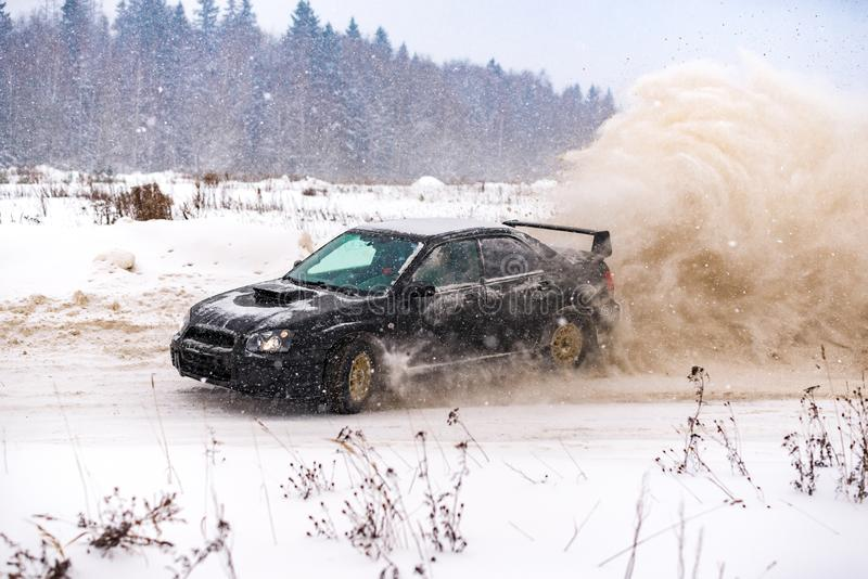 Closeup of car drifting in winter on the road covered with snow stock photo