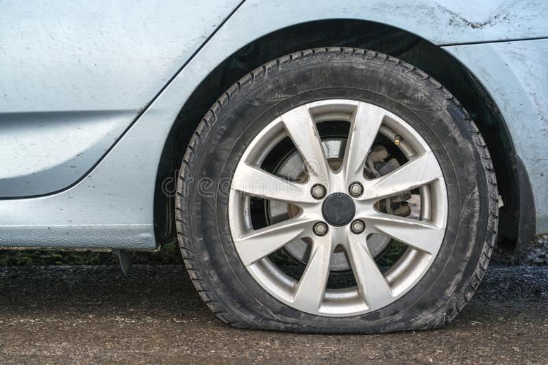 Closeup car flat tire in rainy day on road stock image