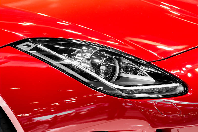 Closeup of car headlight in night. The front lights of the red s. Ports car. Car`s light stock photography
