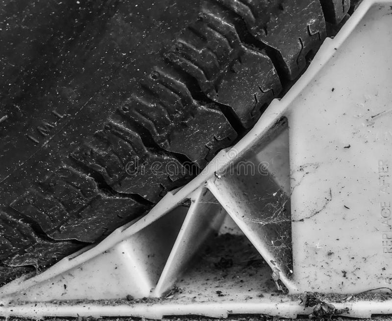 A tire on a wheel stop in black and white royalty free stock photos