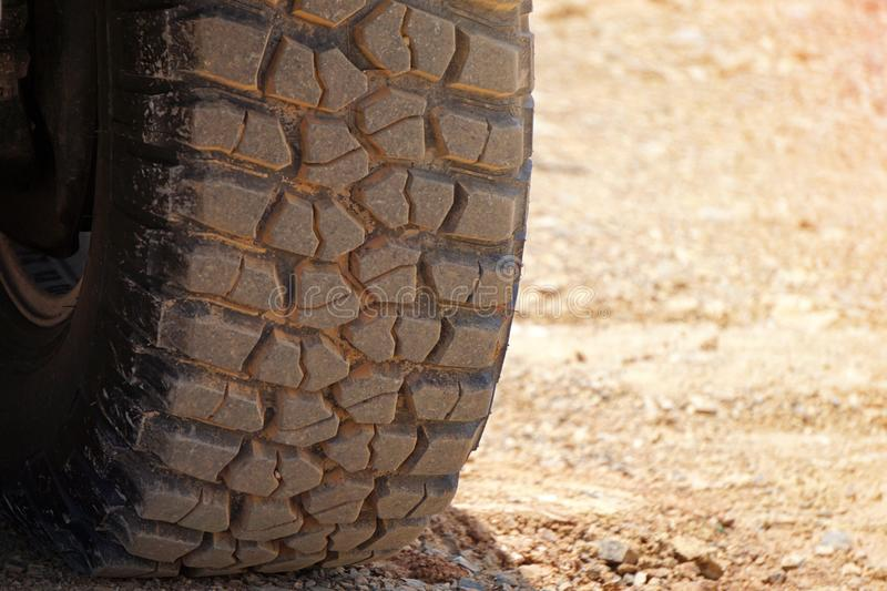 Closeup of car tires. On brown clay road, Space for text royalty free stock images
