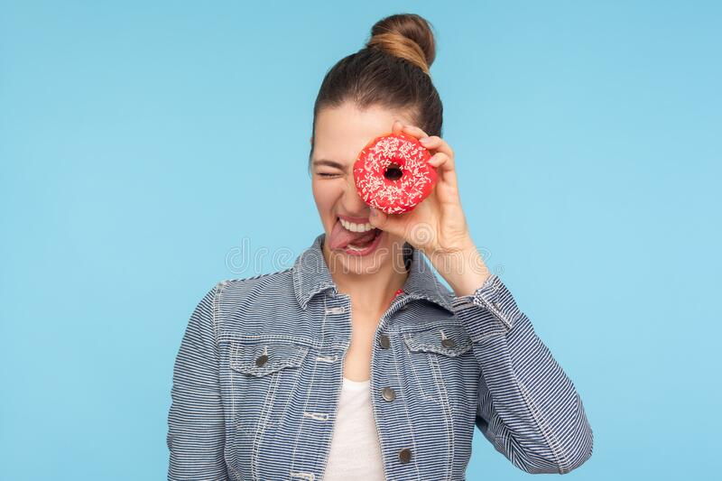 Closeup of carefree amused girl with hair bun peeking through doughnut and sticking out tongue, making face having fun with snack stock photography