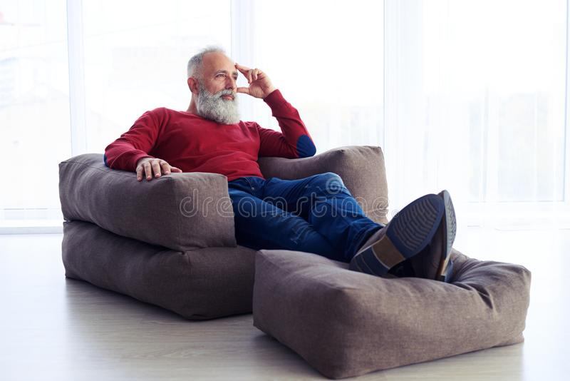 Carefree man relaxing in armchair next to the window at home royalty free stock photos