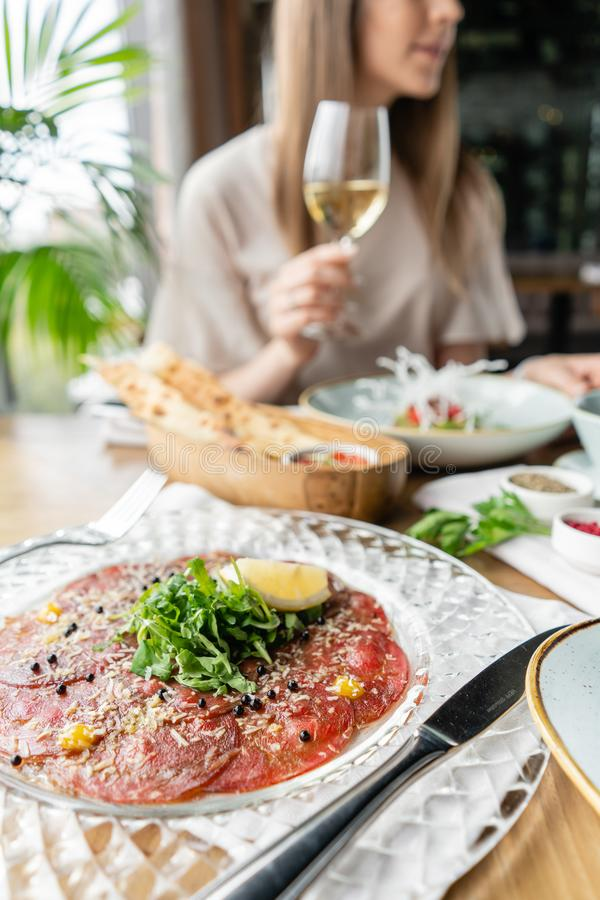 Closeup carpaccio, meat plate in the restaurant. Variety of dishes on the table. Italian cuisine royalty free stock image