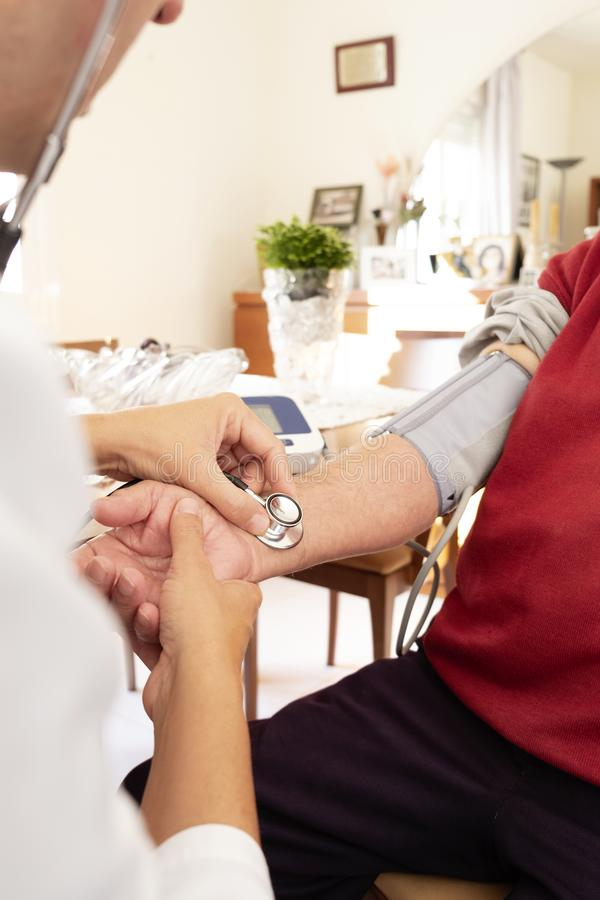 Doctor measuring the blood pressure of a senior. Closeup of a caucasian doctor man, in a white coat, measuring the blood pressure of a senior caucasian patient royalty free stock photo