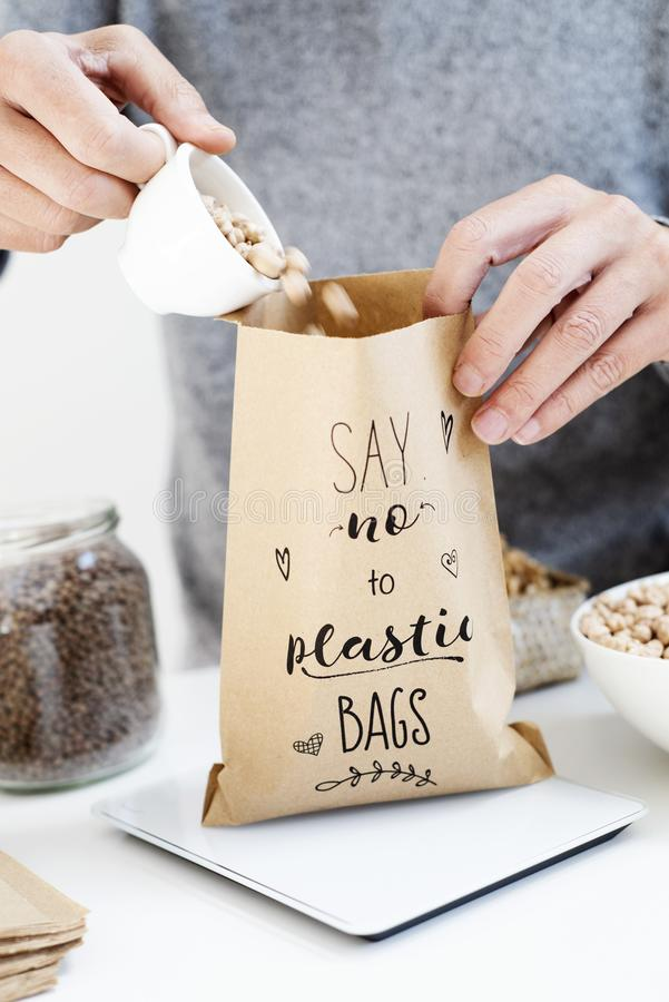 Text say no to plastic bags in a paper bag. Closeup of a caucasian man putting some dry chickpeas on a brown paper bag, with the text say no to plastic bags stock image