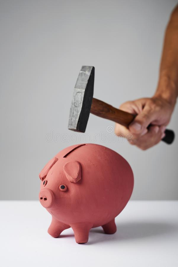 Man about to break a piggy bank with a hammer royalty free stock image