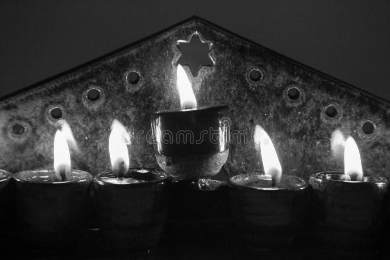 closeup Ceramic hanukiah lit with 4 candles and shamash in b stock image